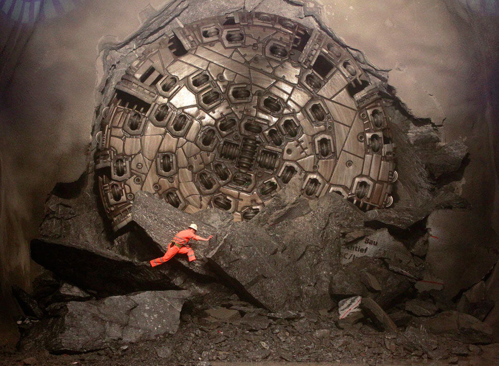 A miner climbs on excavated rocks after a giant drill machine broke through at the final section Sedrun-Faido, at the construction site of the NEAT Gotthard Base Tunnel March 23, 2011.